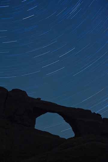 Star trails over Sunset Arch, Arches National Park, Utah.