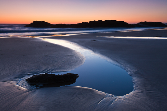 Low tide leaves behind pools of water at twilight on the Oregon coast.